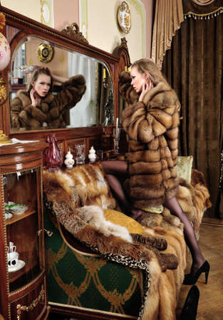 Beautiful naked woman in fur coat  at the mirror. Luxurious classical interior. Stock Photo - 12440237