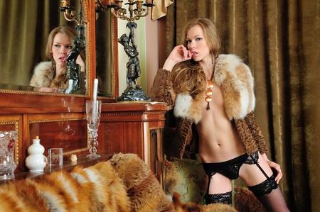 femme se deshabille: Belle femme nue dans manteau de fourrure dans le miroir. Int�rieur classique luxueux.