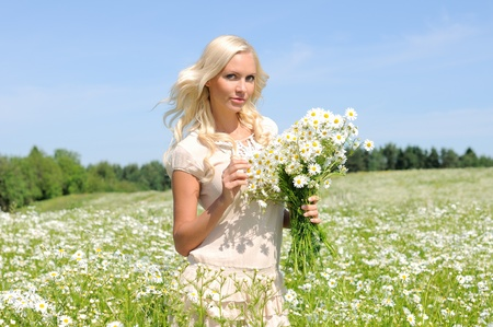 beautiful young woman at the meadow with bunch of  chamomiles. photo