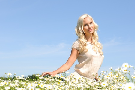 beautiful young woman at the meadow with  chamomiles. photo