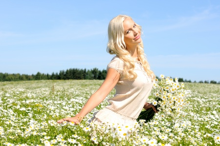beautiful young woman at the meadow with bunch of  chamomiles. Stock Photo - 12718661