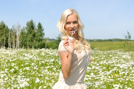 Young woman on the meadow with bubbles photo