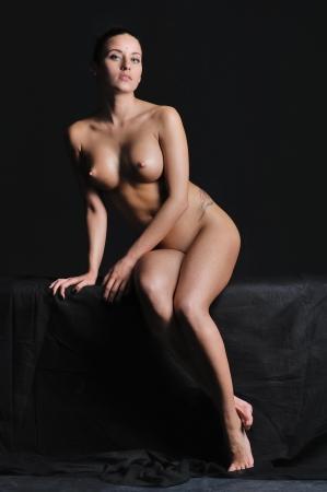 cuerpos desnudos: Hermosa mujer sentada en el estudio oscuro
