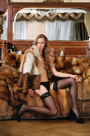 undressed: Beautiful woman in fur coat in a luxurious classical interior. Stock Photo