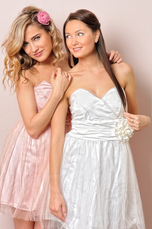 Portrait of the two beautiful woman in chic dresses. photo