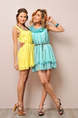 yellow dress: Two beautiful women in summer dresses. Studio  portrait.