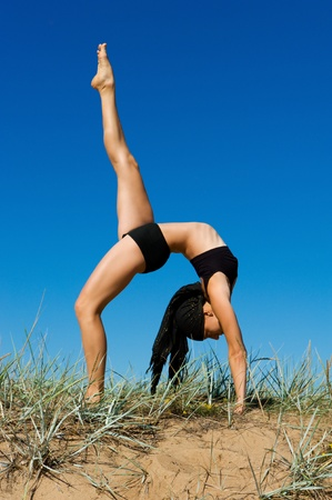 Young beautiful woman  doing exercises  outdoor. photo