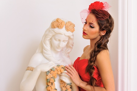 diosa griega: Retrato de la mujer hermosa en vestido rojo de pie cerca de la estatua antigua.