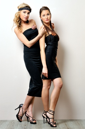 Two beautiful women in a black dresses  Studio portrait  photo