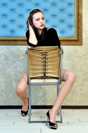 voluptuosa: Retrato de la hermosa mujer sentada en la silla en un hermoso interior.