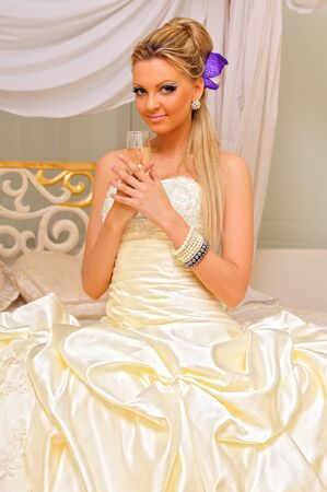 The bride in a wedding dress  with glass of champagne in the luxuriant inteior. photo