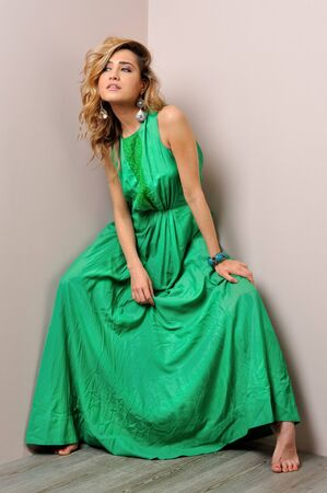 Portrait of the beautiful woman in a long green dress. Studio photoshoot. photo