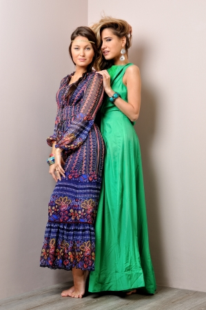 Two beautiful woman posing in a fancy dresses. Sudoi shooting. photo