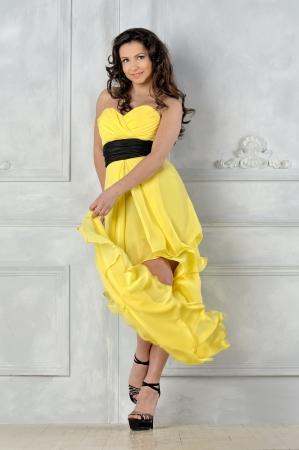 traje de gala: Retrato de la mujer hermosa en vestido de noche amarillo. Foto de archivo