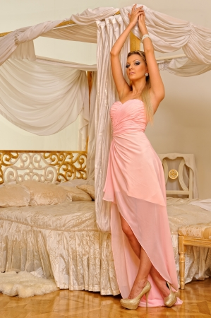 Beautiful woman in long evening dress. Studio luxurious interior. photo
