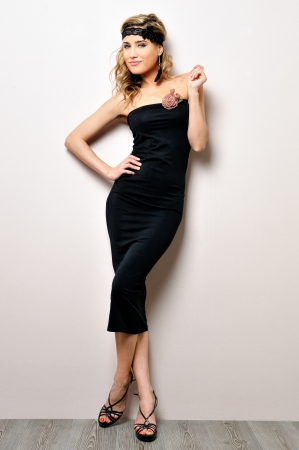 photographing: Portrait of the beautiful woman in a black dress. Studio shooting.