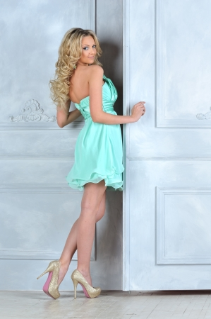 Beautiful blonde in blue short dress at the opening door. Stock Photo