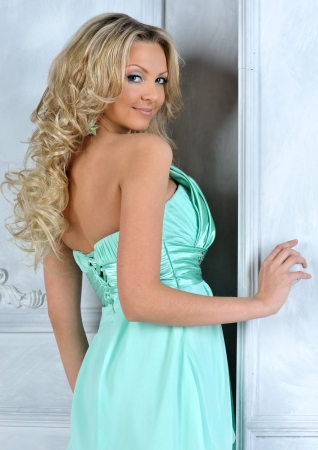 Beautiful blonde woman in blue dress at the opening door. photo