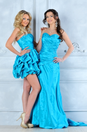 Two beautiful women in long and short evening dresses. photo