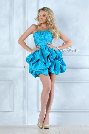 Beautiful blonde girl in short blue evening dress. Stock Photo