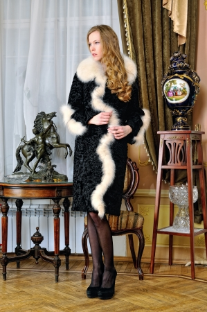 Beautiful woman in fur coat in classical antique interior. photo