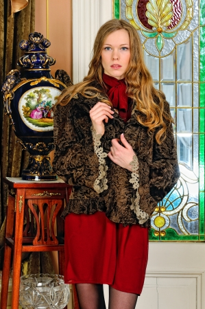 Portrait of the beautiful woman in fur coat. The luxurious antique interior. photo