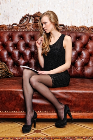 Beautiful woman with book sitting on the sofa in luxuriant antique interior. photo