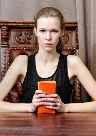 Beautiful woman with book in the antique parlor. photo