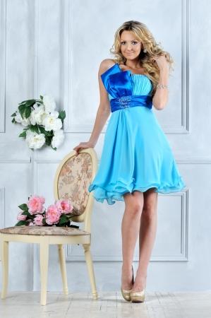 Beautiful blonde woman in blue dress in luxury interior. photo