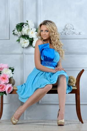 Beautiful blonde woman in blue dress in luxury interior. photo