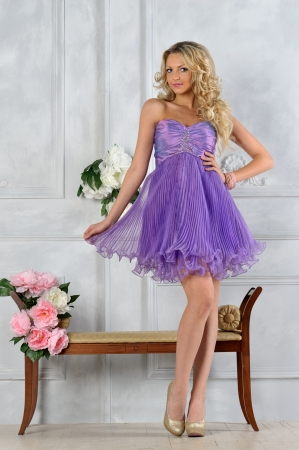 Beautiful blonde woman in lilac dress in luxury interior. photo