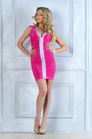 evening gowns: Beautiful blonde woman in a pink dress at the white door. Stock Photo