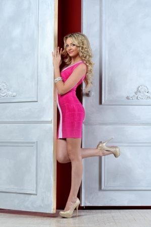 Beautiful blonde woman in a pink dress at the opened white door. photo