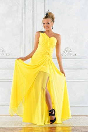 Beautiful blonde woman in a yellow evening dress.