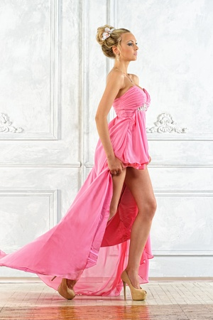 Beautiful blonde woman in a pink evening long dress. photo