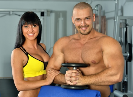 Man and woman are doing exercises in a sport club. Stock Photo