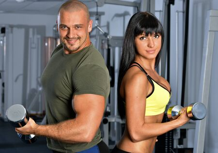 Man and woman are doing exercises in a sport club. photo