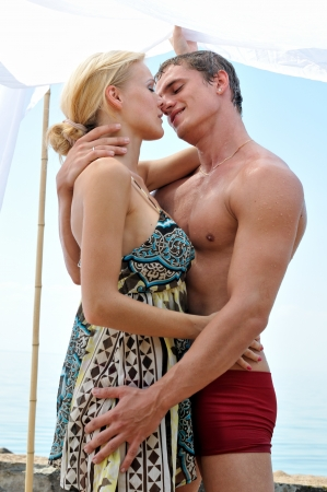 beach kiss: Beautiful woman and man kissing at the beach. Stock Photo