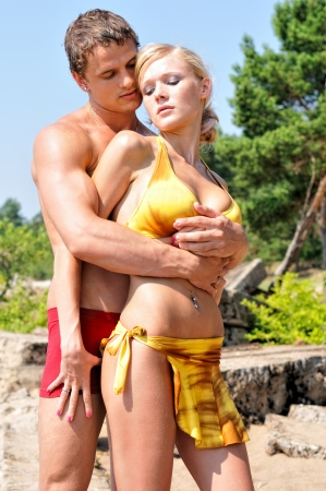 Beautiful man and woman holding on the beach.