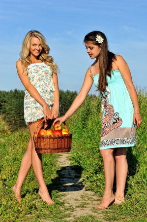 Two beautiful women walking at the meadow with busket with apples. photo