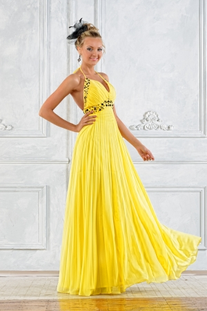 evening gown: Beautiful blonde woman in a long yellow dress.