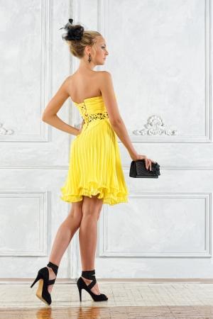 amarillo y negro: Mujer rubia hermosa en un vestido de noche amarillo.