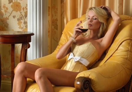 ni�a desnuda: Mujer hermosa en ropa interior con lunas o vino tinto en interior de lujo. Foto de archivo