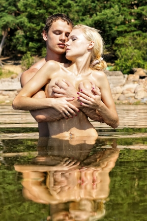 Beautiful nude man and woman kissing in the water outdoors.