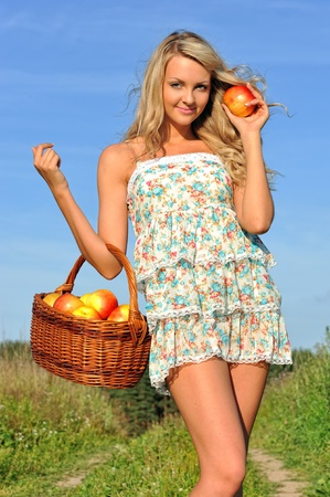Beautiful blonde walking at the meadow with busket with apples. photo