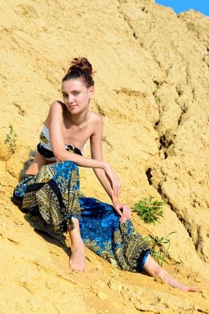 beach wear: Beautiful woman sitting on the sand outdoors.