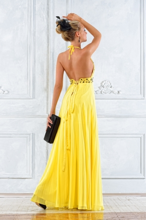 evening dress: Beautiful blonde woman in a long yellow dress.