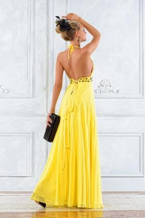 traje de gala: Hermosa mujer rubia con un vestido amarillo de largo.