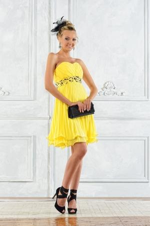 lussureggiante: Bella donna bionda in un abito da sera giallo.