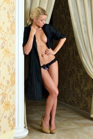 Beautiful nude blonde woman in black silk robe in luxury interior. Stock Photo